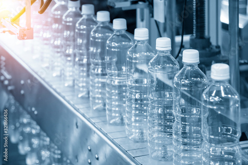 Photo The PET bottles in the rail on the conveyor belt for filling process in the drinking water factory