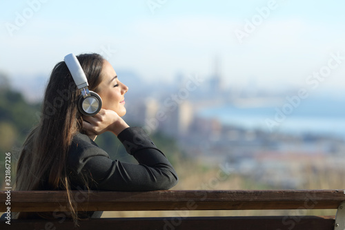Photo Businesswoman relaxing listening to music outdoors