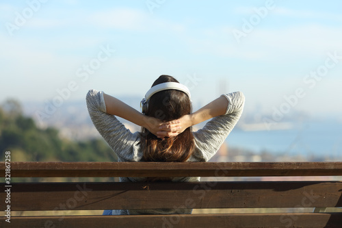 Photo Back view of a woman relaxing listening to music on a bench