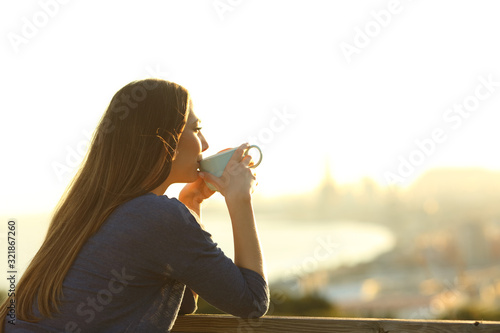 Obraz Girl drinking coffee contemplating views at sunset - fototapety do salonu