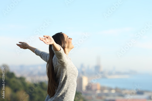 Happy woman stretching arms breathing fresh air outdoors Canvas Print