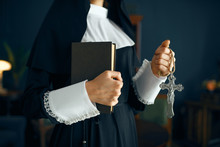 Young Nun In A Cassock Holds Book