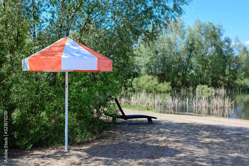 Fényképezés Beach lounger with umbrella for sun protection.