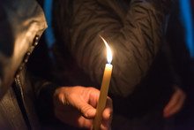Closeup Of People Holding Candle At Night During Church Service