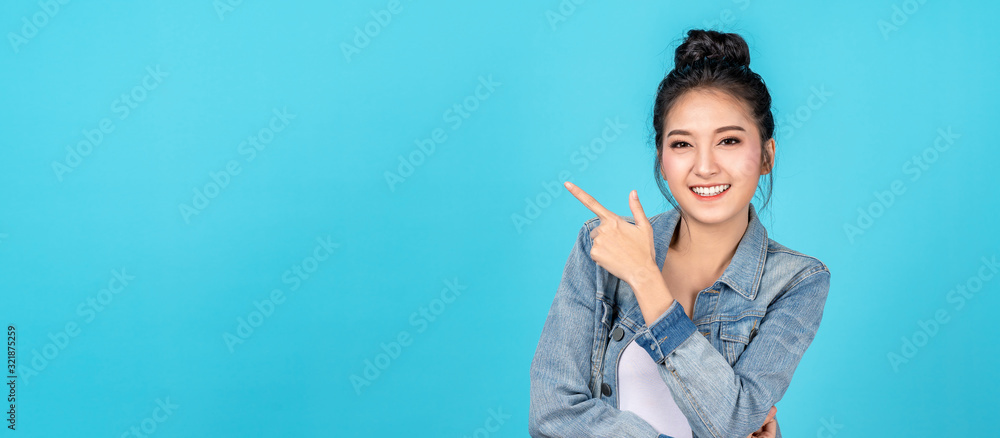 Fototapeta Banner of Happy asian woman standing pointing hands to copyspace on blue background. Cute asia girl smiling wearing casual jeans shirt and finger pointing to aside for present promotions.