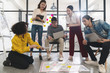 Young creative asian group meeting and looking at project plan lay out on floor discuss or brainstorm business strategy with post note. Workshop for startup team in small office. Happy workplace.