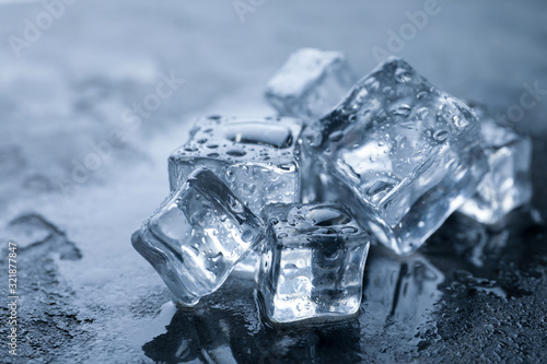 Cuadros en Lienzo Crystal clear ice cubes with water drops on grey table, closeup