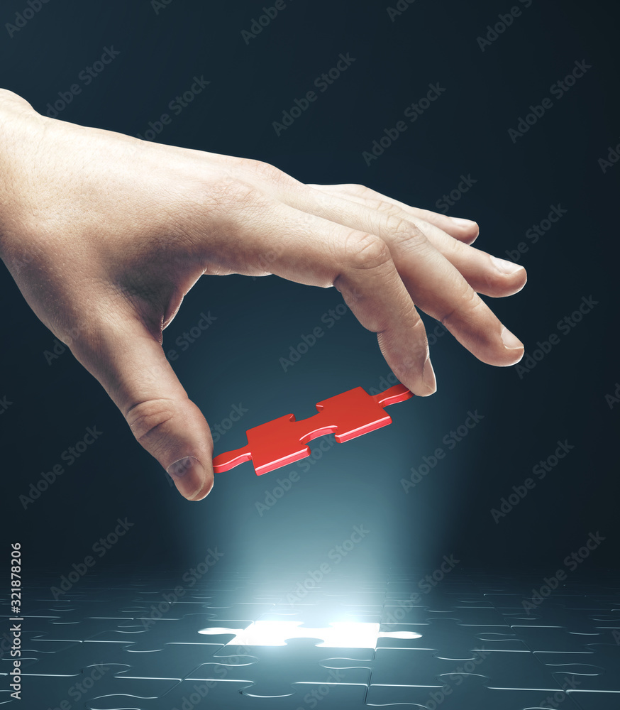 Fototapeta Hand putting red puzzle.