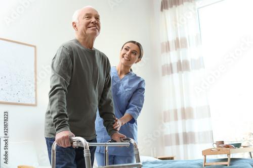 Cuadros en Lienzo Care worker helping elderly man with walker in geriatric hospice
