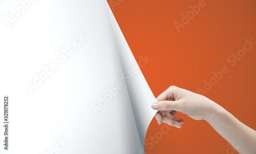 Woman hand turning orange page Wallpaper Mural