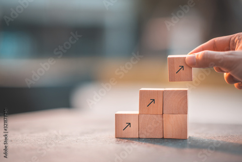 Fototapeta Business concept for growth success process. Hand arranging wood block stacking as step stair at office.  obraz