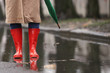 Leinwanddruck Bild Woman in rubber boots with umbrella walking outdoors on rainy day, closeup. Space for text