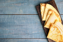 Fresh Thin Pancakes On Blue Wooden Table, Top View. Space For Text