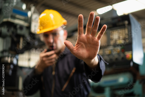 Photo Selective focus of industrial worker in factory site gesture keep out while communicating with a walkie talkie, concept restricts access in industrial factory, working profession, factory restriction