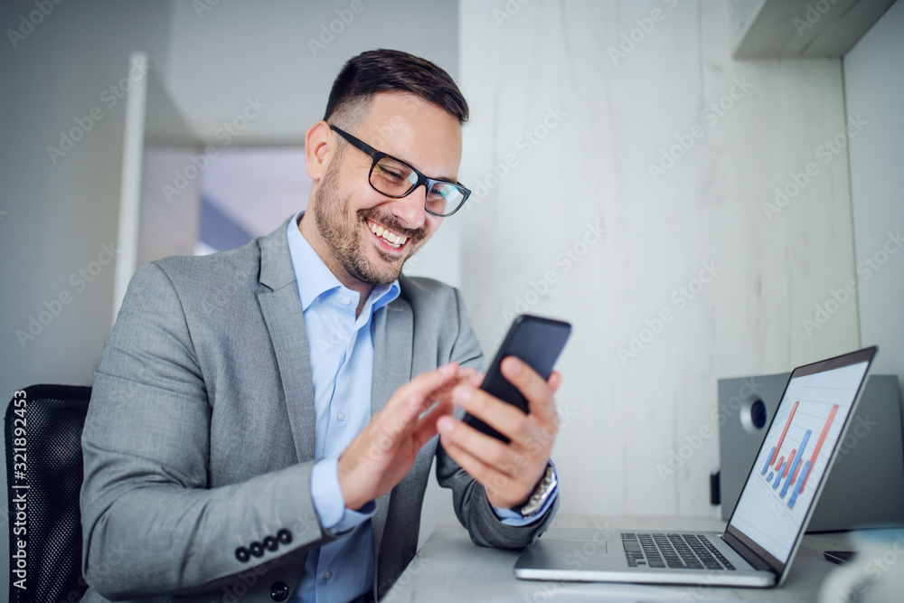 Fototapeta Handsome caucasian classy unshaven businessman in suit and with eyeglasses using smart phone while sitting in office. On table is laptop with chart on it.