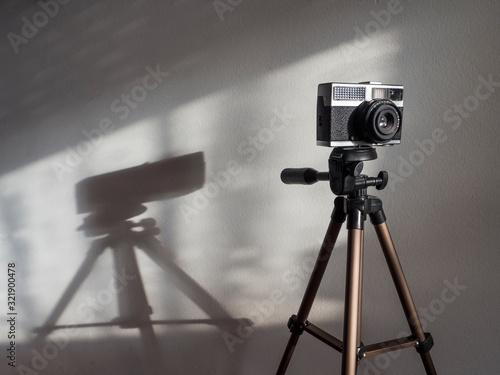 Vintage camera on a tripod under the sun ligth Canvas Print
