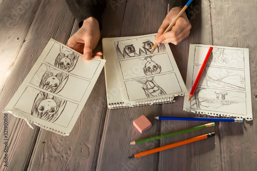 Artist drawing an anime comic book in a studio. Wooden desk, natural light. Creativity and inspiration concept. - 321900806