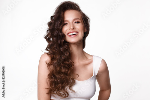 Foto Beautiful young girl in white dress with natural make-up, hair curls and smile