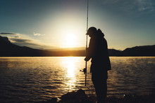 Silhouette Fisherman Wirh Fishing Rod At Sunrise Sunlight, Outline Man Enjoy Hobby Sport On Evening Lake, Person Catch Fish On Pond On Background Night Sky, Fishery Concept