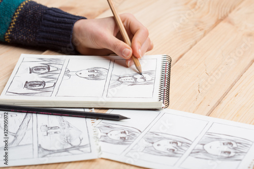 Artist drawing an anime comic book in a studio. - 321905072
