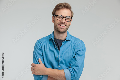 Stampa su Tela excited young casual man laughing and crossing arms