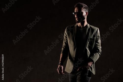 Stampa su Tela cool unshaved guy walking in a fashion light in studio