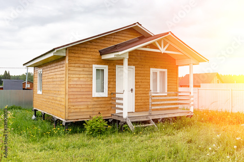 Small tiny wooden frame house with sundeck and white windows and door as a count Canvas Print
