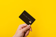 canvas print picture - Female hand holding credit card on yellow background