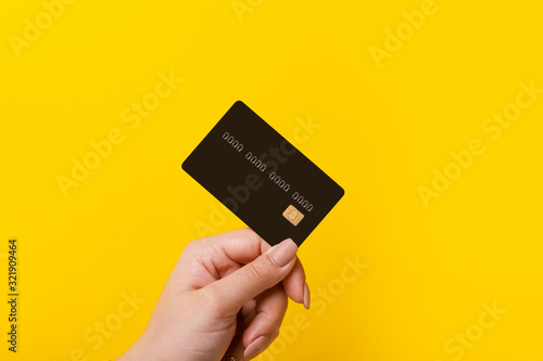 Obraz Female hand holding credit card on yellow background - fototapety do salonu