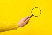 Magnifier In Hand  Over Yellow Background