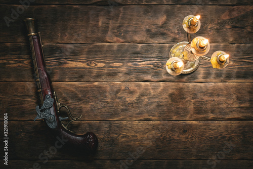 Old musket gun on pirate desk table in the light of burning candle concept background with copy space Wallpaper Mural