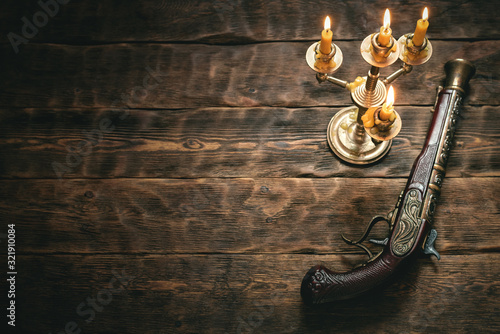 Photo Old musket gun on pirate desk table in the light of burning candle concept background with copy space