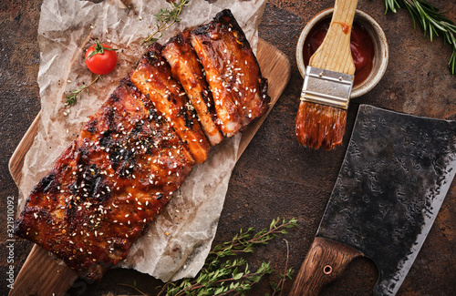 Fototapeta Delicious barbecued ribs seasoned with a spicy basting sauce and served on chopping board. obraz