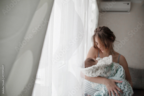 Mother holding the 3 month baby wrapped in a cozy blanket near the window and cr Fototapet
