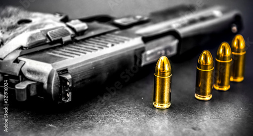 Fototapeta Bullets and handcuffs. Close-up of 9mm pistol. Gun and weapon with bullets amunition on black backround. obraz