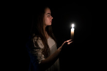 A Young Girl In An Old White Dress Holding A Candle In Her Hand. Side View. Dark Background. Scary Horror Concept.