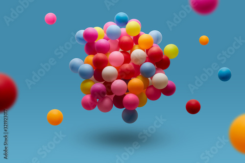 Colorful balls levitation in mid air on blue background Fototapeta
