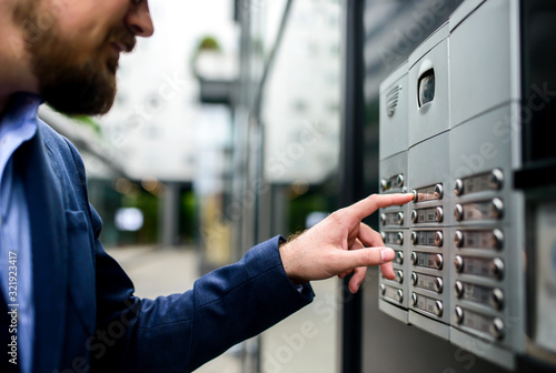 Man pushing the button and talking on the intercom Fototapet