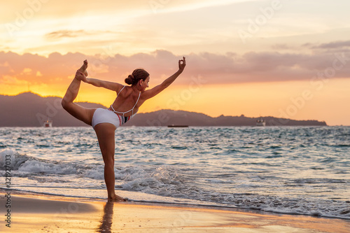 Valokuvatapetti Woman practices yoga at seashore
