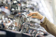 Woman is open faucet. Customer hand touches, chooses a new sink faucet in the kitchen or bathroom at appliances store, close up, soft focus.