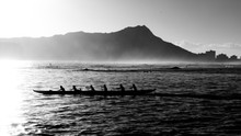 Outrigger Canoe Crews At Sunrise At Waikiki In Monochrome As Silhouettes