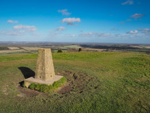 Triangulation Point At The Top Of Beacon Hill, Burghclere, Near Newbury Looking East Across Waterhsip Down And Home Counties Countryside With Clouds Set Against A Blue Sky, Berkshire, UK