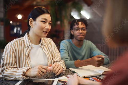 Obraz Multi-ethnic group of three business people working on project while sitting at table in cafe, copy space - fototapety do salonu