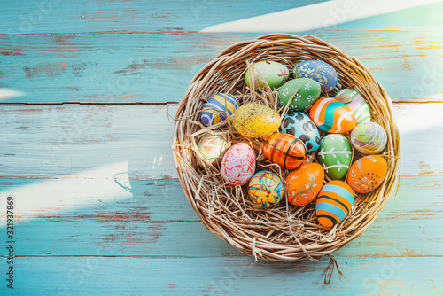 Colorful Easter eggs in basket on wooden background Wallpaper Mural