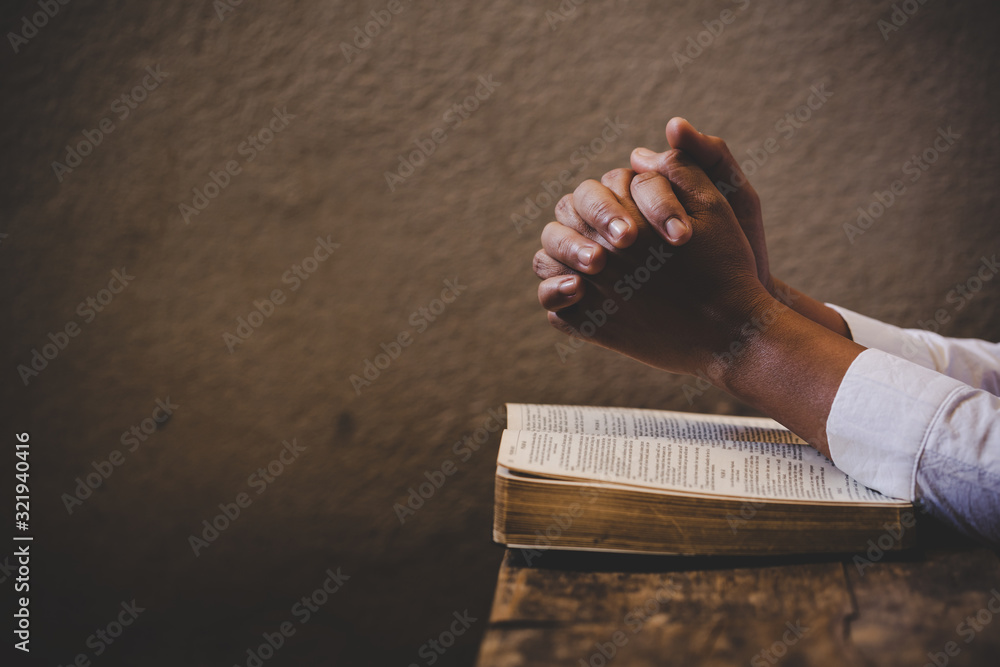 Fototapeta Hands folded in prayer on a Holy Bible in church concept for faith