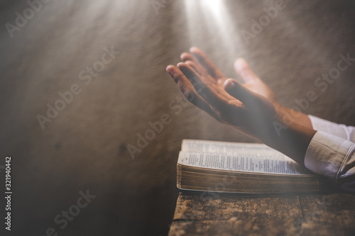 Fotografie, Obraz Hands folded in prayer on a Holy Bible in church concept for faith