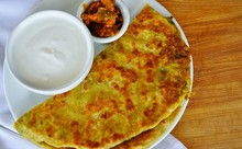 A Plate With Aloo Paratha Bread Stuffed With Potatoes And A Dish Of Yogurt At An Indian Restaurant
