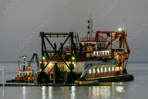 Vászonkép Harbor dredging vessel boat working under glowing lights during calm ocean conditions with reflection in the water surface