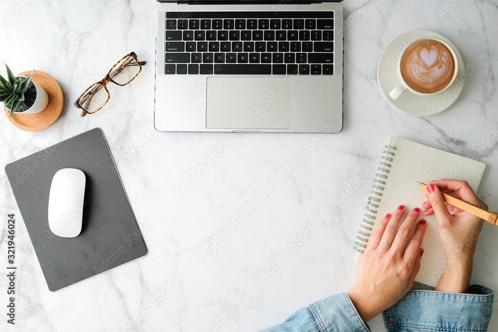 Fototapeta Flat lay workspace. Woman hand with coffee cup, smartphone, computer, notebook, planner and stationary with copy space on marble table background. Top view.