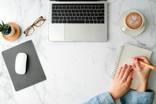 Flat Lay Workspace. Woman Hand With Coffee Cup, Smartphone, Computer, Notebook, Planner And Stationary With Copy Space On Marble Table Background. Top View.